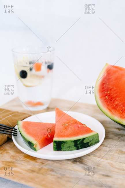 Slices of delicious juicy watermelon placed on plate in kitchen on wooden table