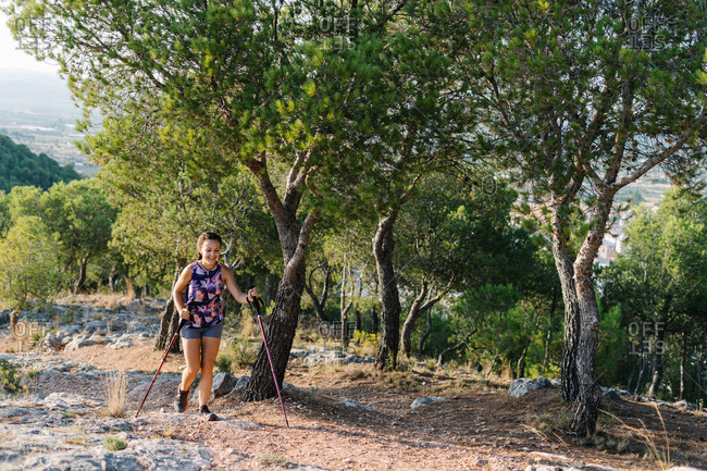 Positive young athletic female in activewear hiking with trekking poles on stony trail in green forested mountainous terrain