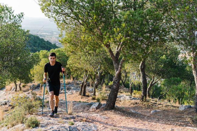 Positive young athletic man in activewear hiking with trekking poles on stony trail in green forested mountainous terrain