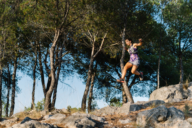 From below side view of active sportive young woman jumping high over rocky trail while running in green forest in mountains