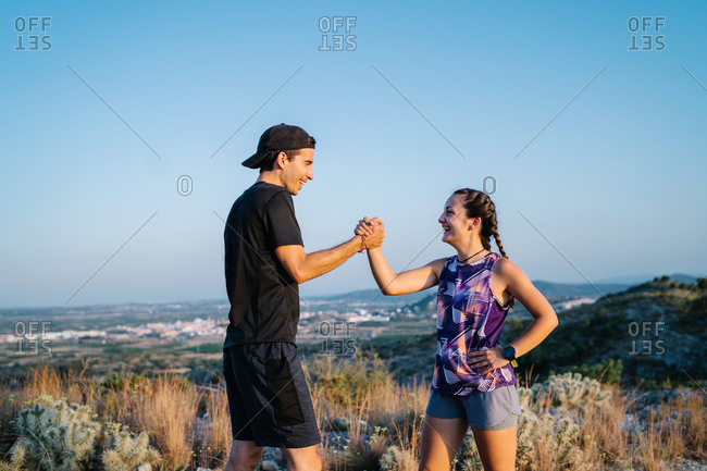 Side view of happy young man and woman in activewear greeting each other with wrestling arms gesture while preparing for trail running together in mountainous terrain