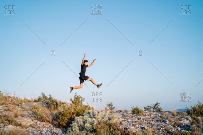From below side view of active sportive young man jumping high over rocky trail while running in mountains