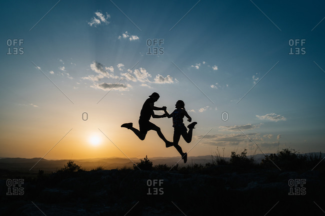 Side view silhouettes of unrecognizable male and female friends jumping high above ground while having fun and enjoying freedom in hilly terrain against sunset sky