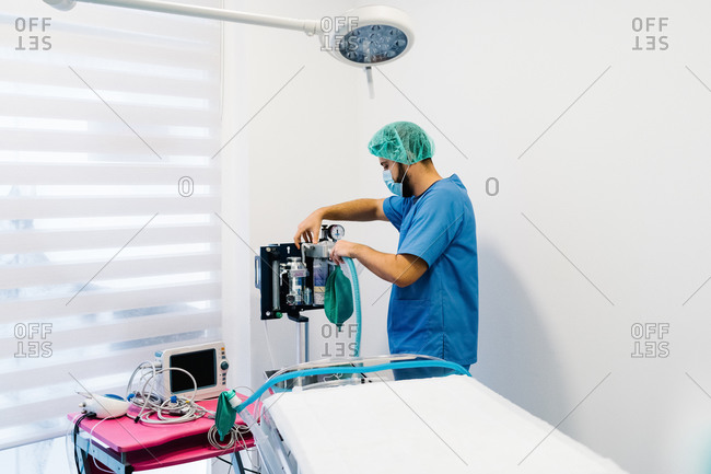 Side view of male vet doctor in uniform and mask preparing anesthesia machine for surgery in bright operating theater in veterinary clinic