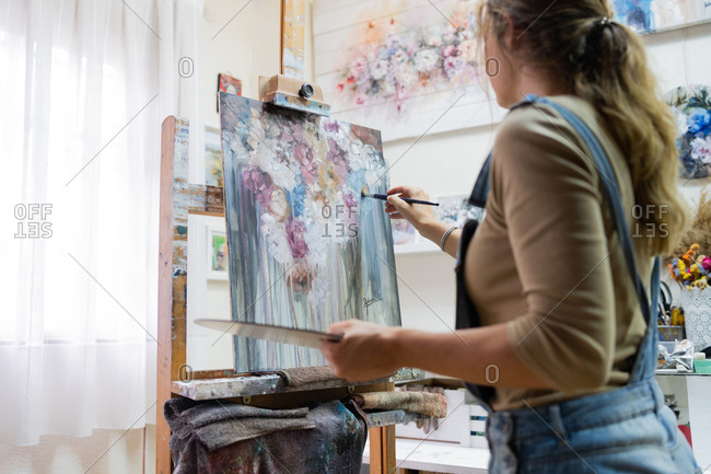 Side view of crop female artist standing near easel and drawing colorful picture with paints while working in creative workshop