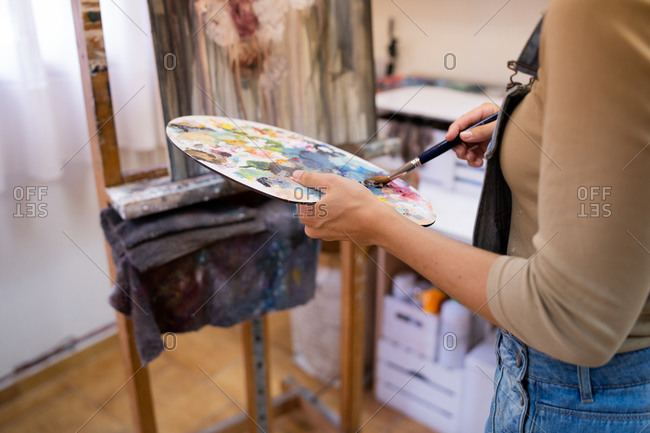 Crop anonymous artist taking paint from colorful art palette while creating artwork in art studio