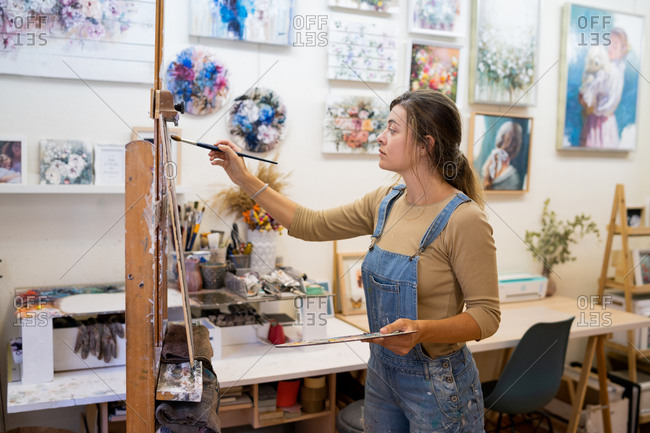 Side view of female artist standing near easel and drawing colorful picture with paints while working in creative workshop