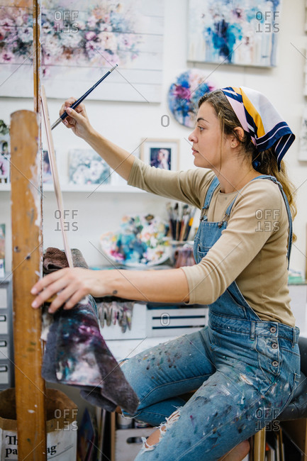 Side view of female artist sitting near easel and drawing colorful picture with paints while working in creative workshop