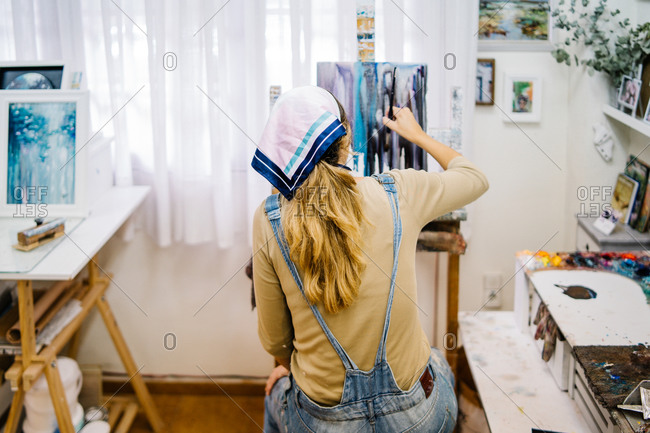 Back view of anonymous female artist sitting near easel and drawing colorful picture with paints while working in creative workshop