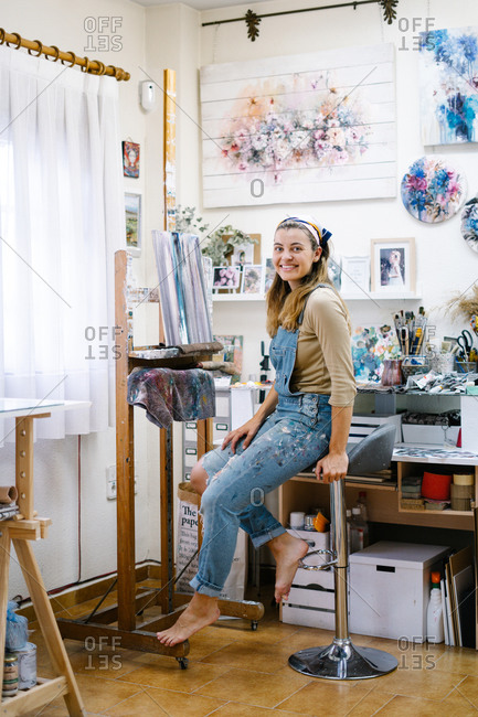 Side view of cheerful female artist in denim overall looking at camera while sitting near easel and painting picture with paintbrush in creative atelier