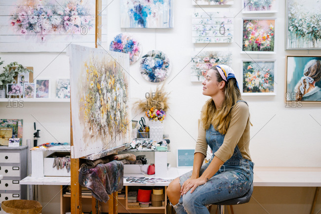 Side view of cheerful female artist in denim overall looking at painting in creative atelier