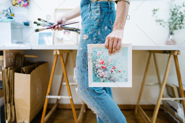 Side view of anonymous female artist standing near easel and holding a colorful paint and brushes in creative workshop