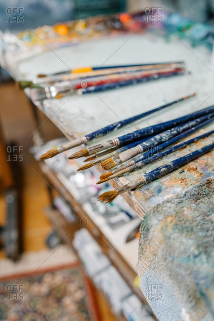 Various brushes smeared with colorful paints placed on table on workplace of artist in creative atelier