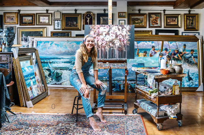 Cheerful female artist in denim overall looking at camera while sitting near easel and painting in creative atelier