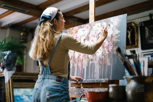 Back view of female artist standing near easel and drawing colorful picture with paints while working in creative workshop