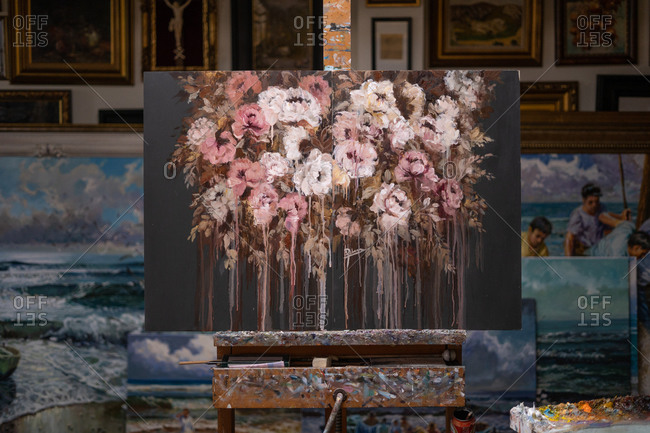 Beautiful floral painting on canvas placed on easel at workplace in creative art workshop