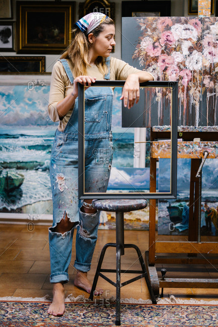 Full length of creative young female artist in denim overall holding empty frame while standing near easel with picture in workshop with paintings