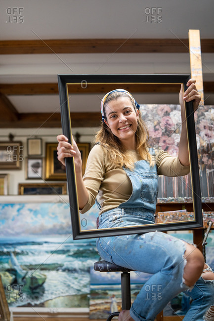 Creative young female artist in denim overall holding empty frame while sitting near easel with picture in workshop with paintings