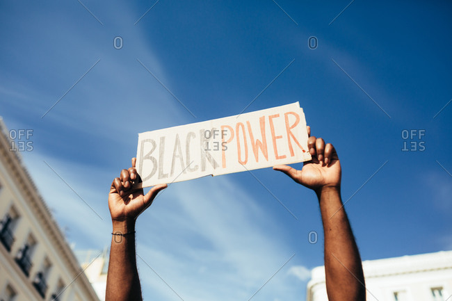 "Unrecognizable man protesting at a rally for racial equality holding a ""Black Power"" poster. Black Lives Matter."