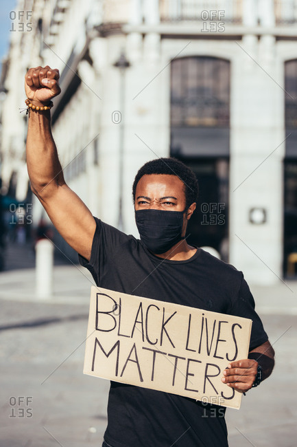 Man protesting at a rally for racial equality holding a poster against racism. Black Lives Matter.