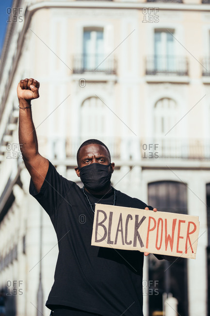 "Man protesting at a rally for racial equality holding a ""Black Power"" poster. Black Lives Matter."