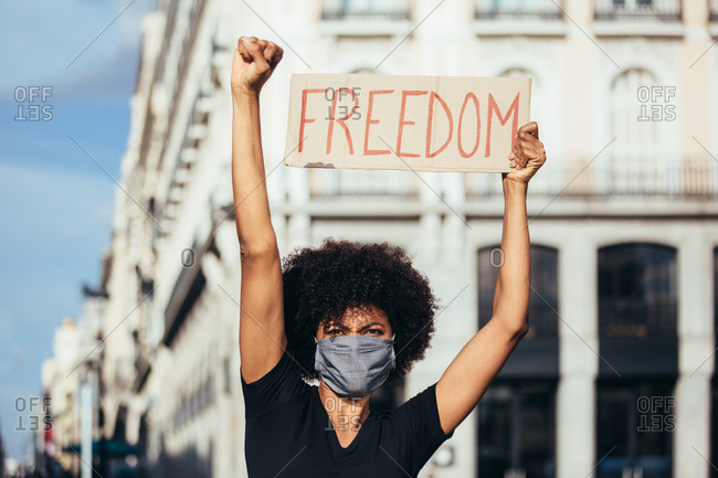 "Afro woman protesting at a rally for racial equality. She is raising fist holding a sign with the word ""Freedom"". Black Lives Matter."