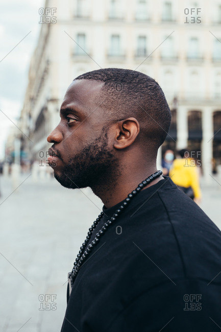 Side view portrait of serious black man looking away in urban scenery