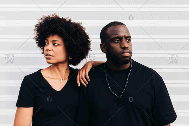 Black cool couple posing over white background looking at camera