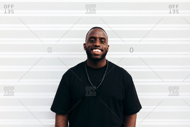 Happy black man posing and smiling over white background and looking at camera