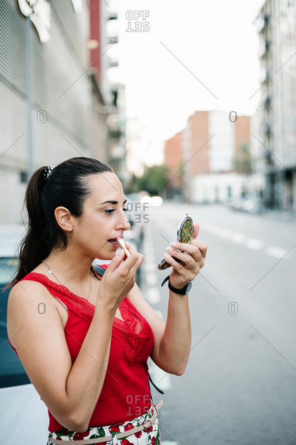 Modern brunette in red blouse looking at reflection on mirror while standing on city street and applying lipstick