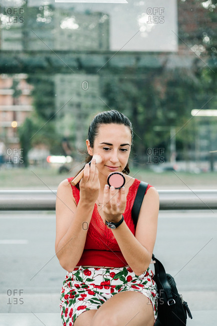 Modern brunette in red blouse looking at reflection on blush mirror while standing on city street and applying blush with brush