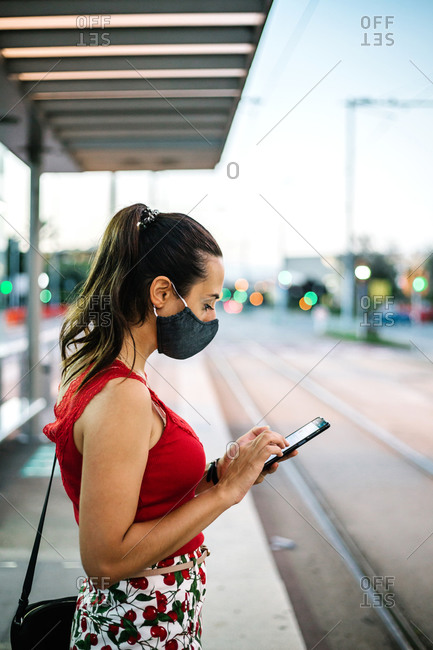 Side view of young female in black protective mask browsing smartphone while standing on railway platform and waiting for train