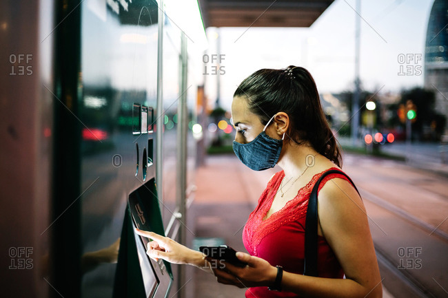 Side view of young female passenger in protective mask with mobile phone buying ticket for public transport on vending machine