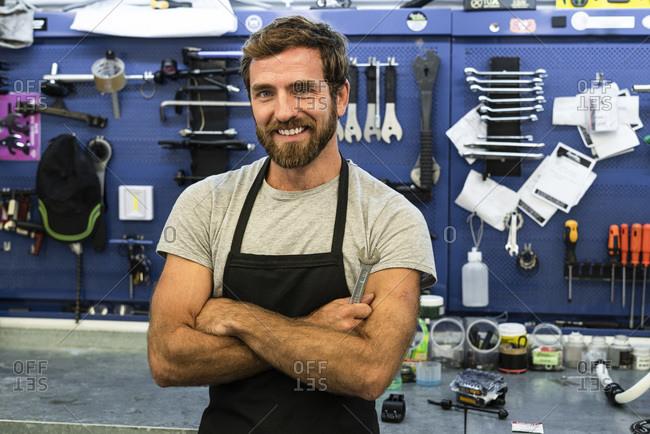 Smiling mechanic standing in workshop