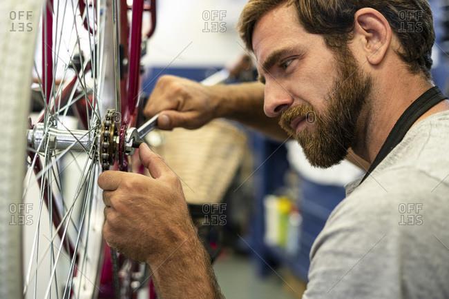 Mechanic repairing bicycle wheel in workshop