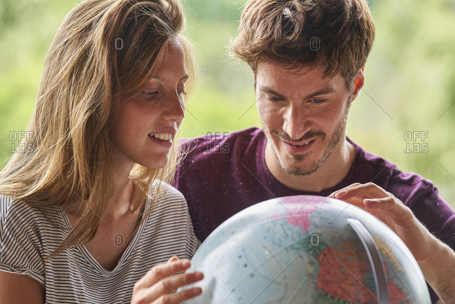 Young couple exploring world globe while sitting in living room