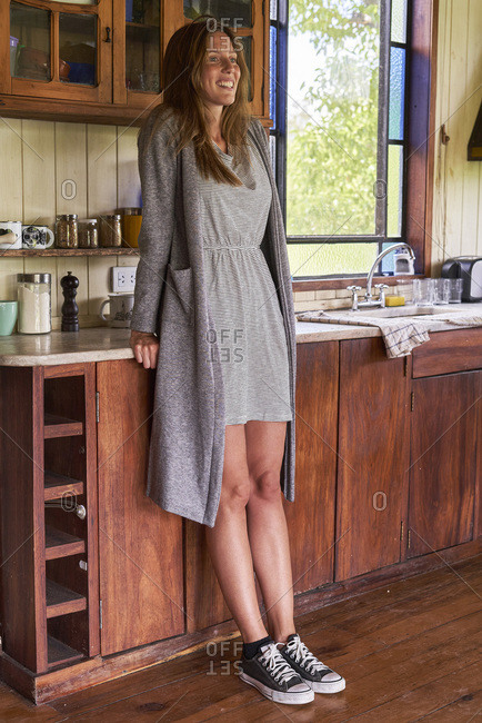 Young woman leaning on kitchen counter