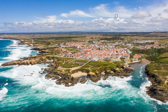 Aerial view of Porto Covo and waves crashing onto rocks, Setubal, Portugal.
