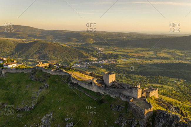 Aerial view of Santa Maria de Marvao perched above a cliff overlooking the countryside at sunset, Portugal.