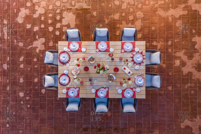 Aerial view of laid table and ten chairs on terracotta floor, Albernoa, Portugal.