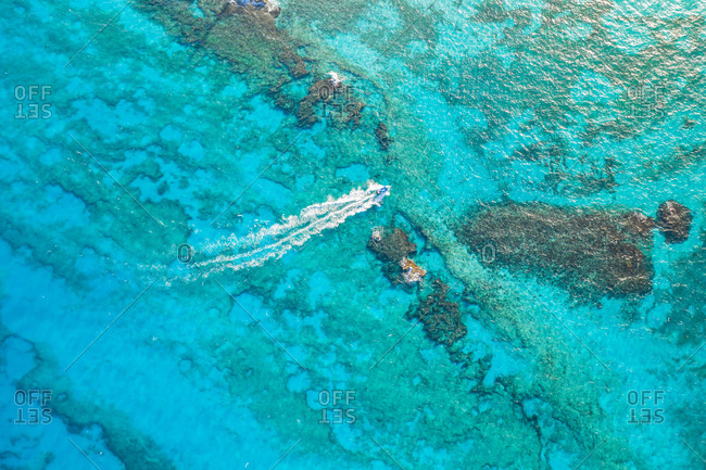 Aerial view of speedboat speeding across coral reef at Punta Cancun in Cancun, Mexico.