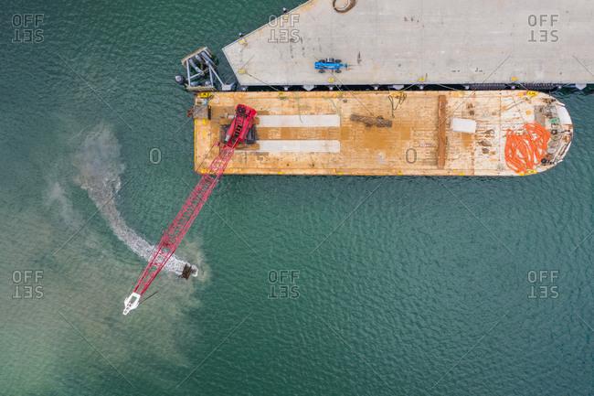 Aerial view of crane on floating platform in the bay of Unalaska, Alaska, USA.