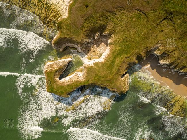 Aerial view of waves crashing on chalk cliffs along Selwicks Bay, York, UK.