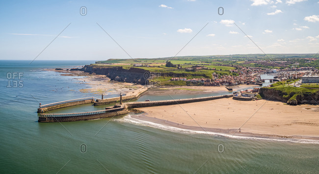 Aerial view of east and west piers each with a lighthouse and beacon, Whitby, UK.