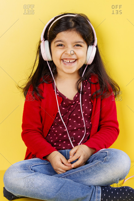 Cute little girl listening to music with her headphones