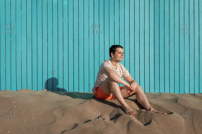 Young man looking away sitting in sand beach with turquoise wall
