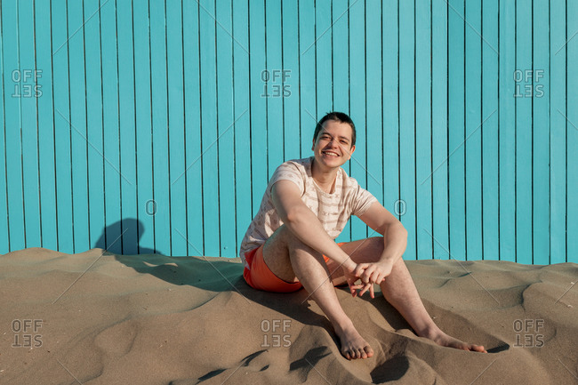 Young man sitting in sand beach smiling at camera in a turquoise wall