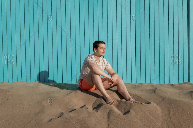 Young man with eyes closed sitting in sand beach in turquoise wall