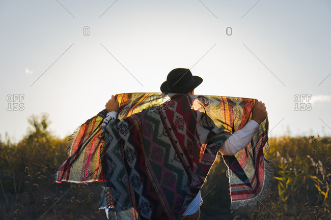 Man standing in a field poses with vintage poncho against the sun