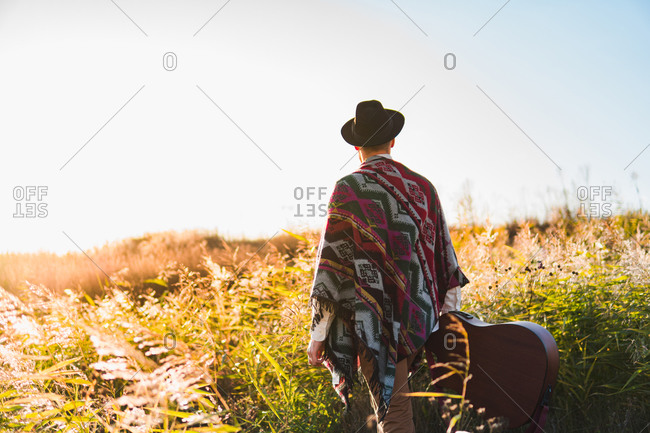 Man with acoustic guitar wearing poncho in a rural area at sunset